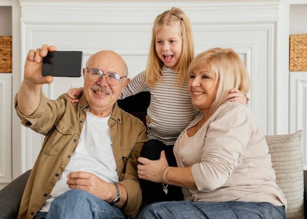 Famille heureuse de plan moyen prenant selfie