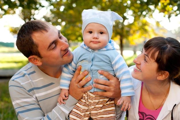 Famille heureuse en plein air - mère, père et fils sourient