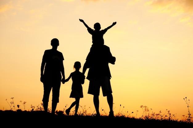 Famille heureuse sur prairie au coucher du soleil de l'été