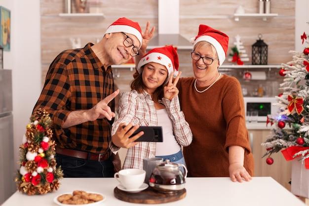 Famille heureuse prenant selfie à l'aide d'un smartphone faisant des expressions drôles
