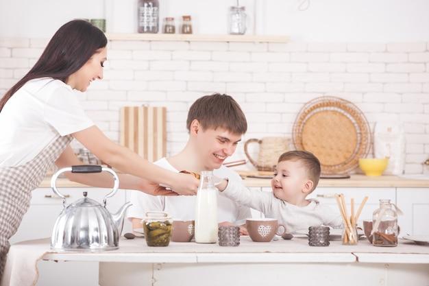 Famille heureuse prenant son petit déjeuner ensemble. jeune famille mangeant à table sur la cuisine. maman, papa et petit bébé mangent.