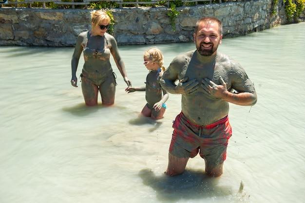 Une famille heureuse prend un bain de boue dans un complexe en turquie.bien-être familial dans la boue thérapeutique