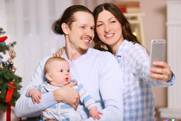 Une famille heureuse prend un selfie sur le sol dans la salle de noël décorée