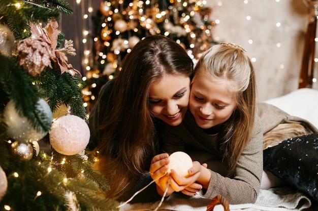 Famille heureuse près de l'arbre de noël maman et fille noël nouvel an