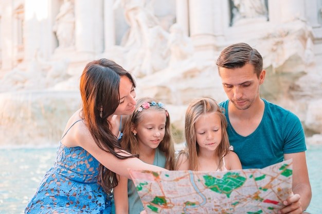 Famille heureuse près de fontana di trevi avec plan de la ville