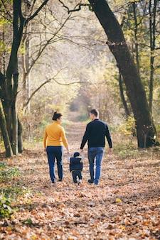 Famille heureuse, profitez de la nature automnale. famille marchant dans un parc en automne avec des feuilles d'automne tombées.