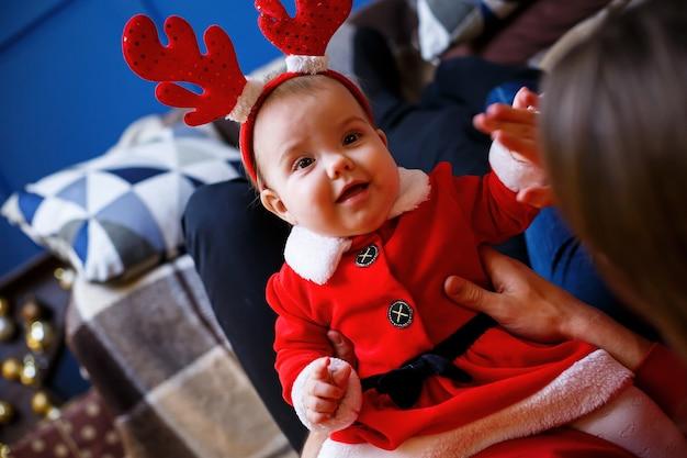 Une famille heureuse en pulls rouges est assise par terre. ambiance de vacances de noël. un enfant en costume de père noël. notion de relation familiale