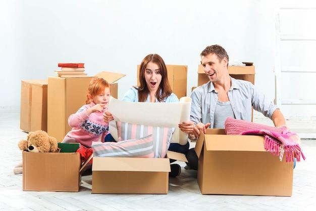 La famille heureuse à la réparation et au déménagement. la famille planant jusqu'à l'hébergement sur fond de caisses