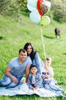 Famille heureuse reste dans la nature et mange un gâteau