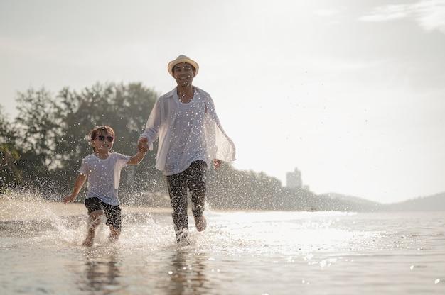 Famille heureuse s'amusant à courir sur la plage au coucher du soleil vacances en famille sur la plage en été voyage