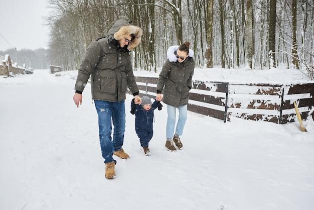 Une famille heureuse s'amuse à l'extérieur près de la maison en hiver. vacances en famille et concept de temps heureux