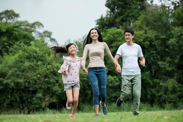 Une famille heureuse s'amuse mère, père et fille courent dans un parc.