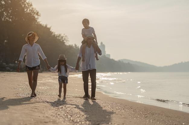 Une famille heureuse s'amuse sur la plage au coucher du soleil père et mère et enfants jouant ensemble