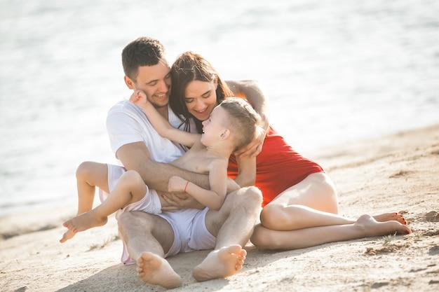 Famille heureuse, s'amuser à la plage. maman, papa, fils et petite fille au bord de la mer. famille joyeuse