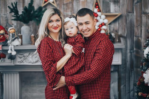 Famille heureuse avec sa petite fille ensemble dans une salle décorée