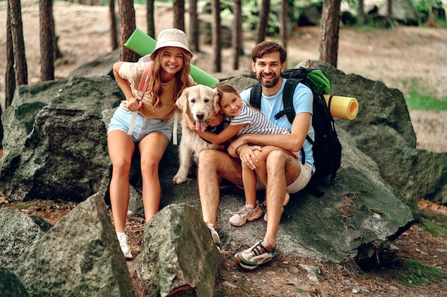 Famille heureuse avec sacs à dos et promenades de chien labrador dans la forêt. camping, voyages, randonnées.