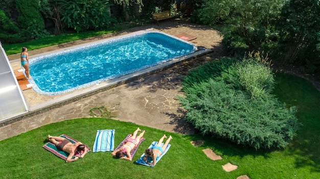 Famille heureuse se détendre au bord de la piscine, vue aérienne du drone par le haut des parents et des enfants s'amuser en vacances, week-end en famille sur la station