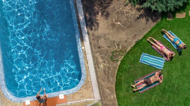 Famille heureuse se détendre au bord de la piscine, vue aérienne d'en haut des parents et des enfants s'amuser en vacances, week-end en famille sur la station