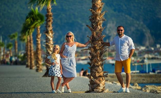 Une famille heureuse se tient sous un palmier au bord de l'eau à fethiye. turquie.