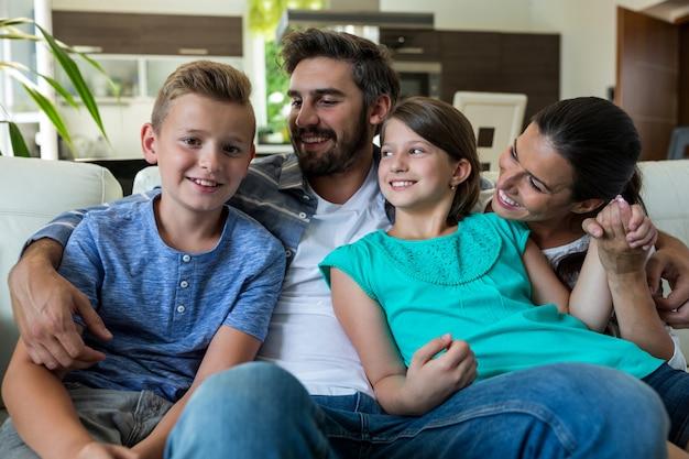 Famille heureuse, séance, bras, autour de, sofa