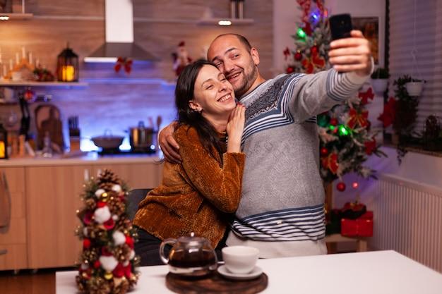 Famille heureuse souriant tout en prenant un selfie à l'aide d'un smartphone moderne