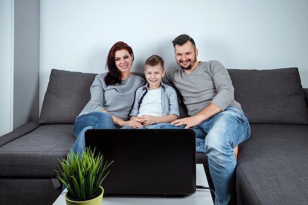 Une famille heureuse sourit en regardant quelque chose dans un ordinateur portable
