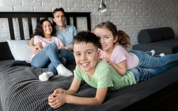 Famille heureuse de tir complet posant ensemble