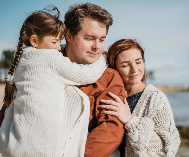 Famille heureuse de tir moyen à la plage