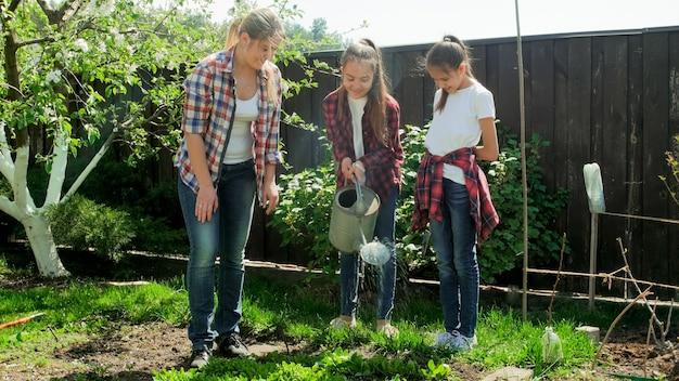 Famille heureuse travaillant dans le jardin et arrosant les légumes.