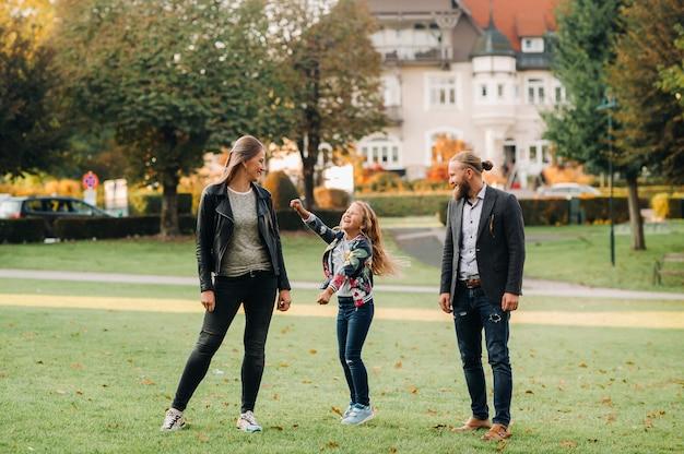 Une famille heureuse de trois personnes court dans l'herbe de la vieille ville d'autriche.une famille se promène dans une petite ville d'autriche.europe.velden am werten zee.