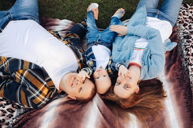 Une famille heureuse de trois personnes s'allonge sur le canapé et profite de la vie ensemble