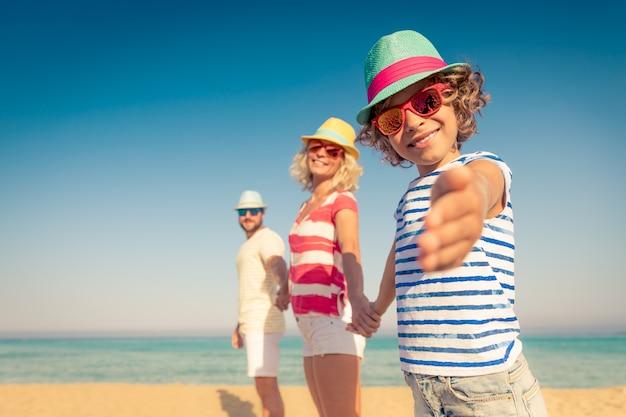 Famille heureuse en vacances d'été gens s'amusant sur la plage