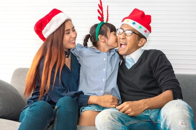 Famille heureuse en vacances et noël, parent et fille s'embrassent et souriant.