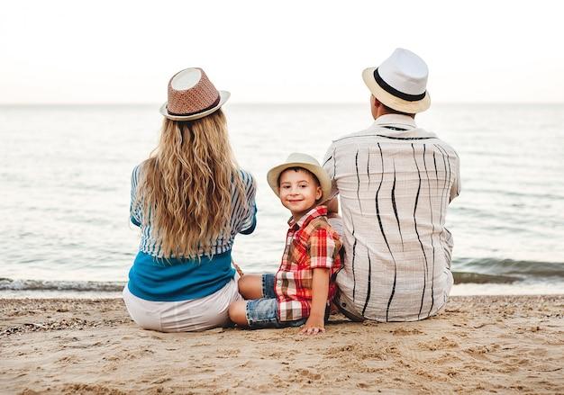 Famille heureuse en vacances. sur la plage se trouve maman, papa et un petit fils. famille en voyage. bisous, sourires.