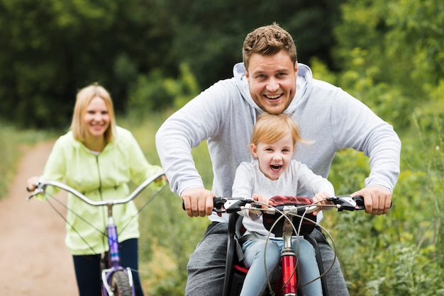 Famille heureuse avec des vélos sur une route forestière