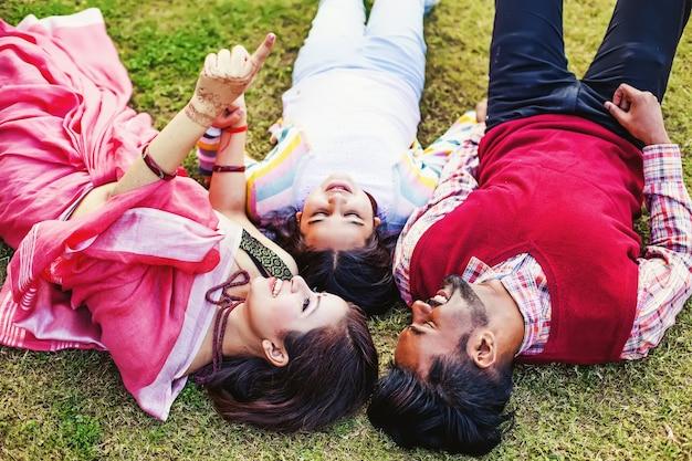 Famille indienne couchée dans le parc en montrant quelque chose