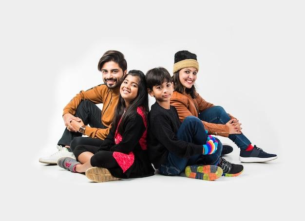 Famille indienne dans des vêtements chauds assis sur fond blanc. prêt pour l'hiver