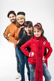 Famille indienne dans des vêtements chauds debout sur fond blanc. prêt pour l'hiver