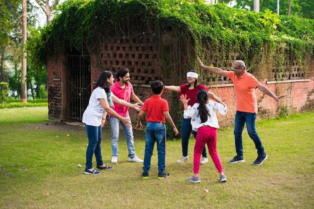 Famille indienne jouant aux yeux bandés ou au jeu de koshimbir andhali dans un parc ou un jardin, famille asiatique multigénérationnelle jouant à des jeux amusants en plein air
