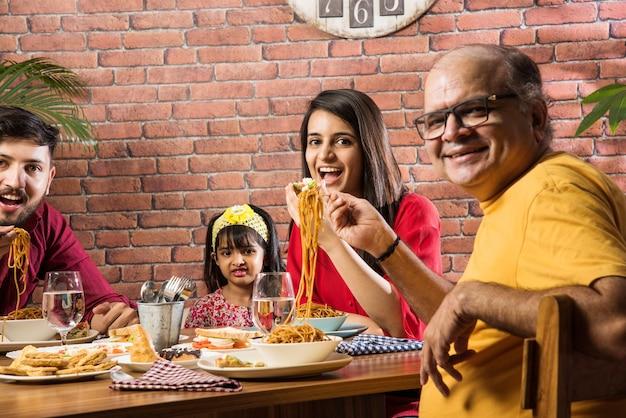 Famille indienne mangeant de la nourriture à la table à manger à la maison ou au restaurant en train de manger ensemble