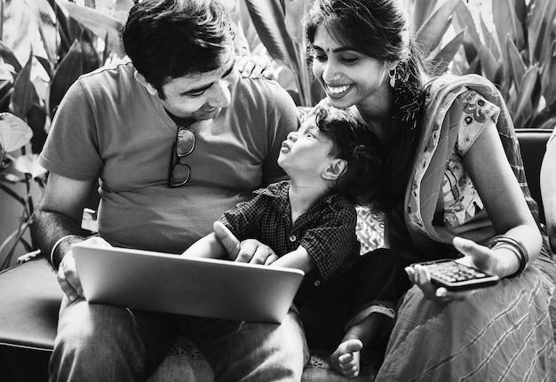 Famille indienne utilisant un ordinateur portable ensemble