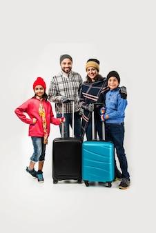 Famille indienne avec valise tout en portant des vêtements chauds, prête pour les vacances d'hiver