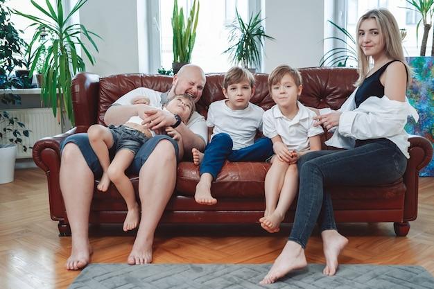 Famille insouciante et heureuse d'hommes et de femmes mûrs avec leurs petits enfants, ils sont assis sur un canapé et s'amusent.