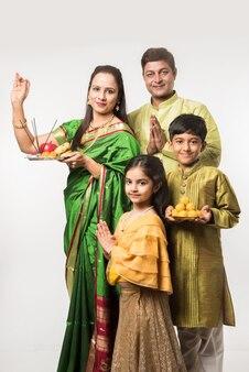 Famille intelligente indienne asiatique accueillant lord ganesha idol lors du festival de ganesh avec pooja thali et des bonbons. debout isolé sur fond blanc