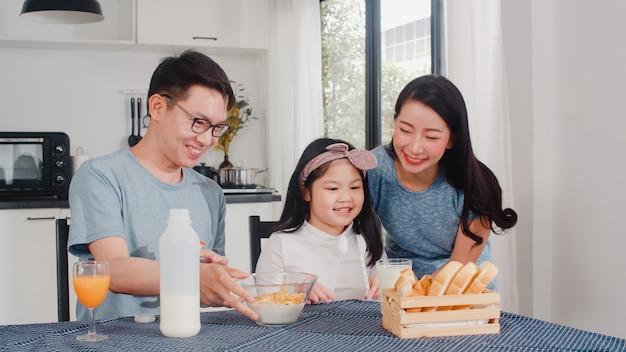 Famille japonaise asiatique prend le petit déjeuner à la maison. maman, papa et fille asiatiques se sentant heureux de parler ensemble tout en mangeant du pain, des céréales de flocons de maïs et du lait dans un bol sur la table dans la cuisine le matin.