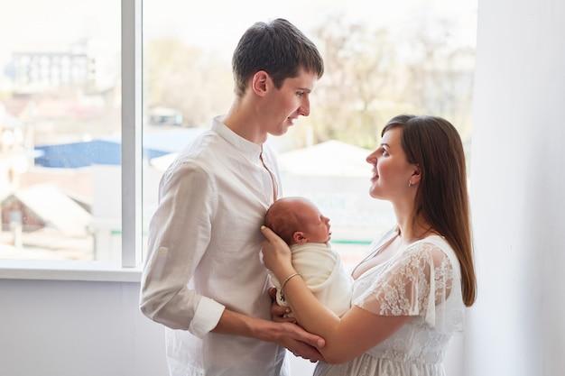 Famille jeunes parents avec la maison du nouveau-né
