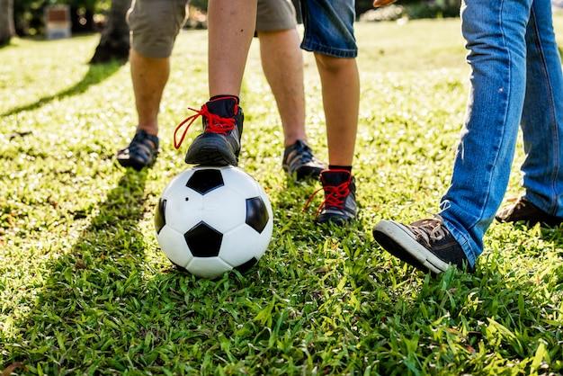 Famille jouant au football dans le jardin
