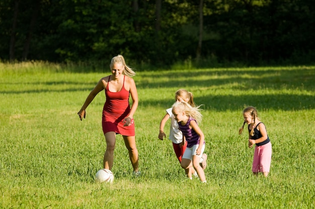 Famille jouant au football dans un terrain en herbe