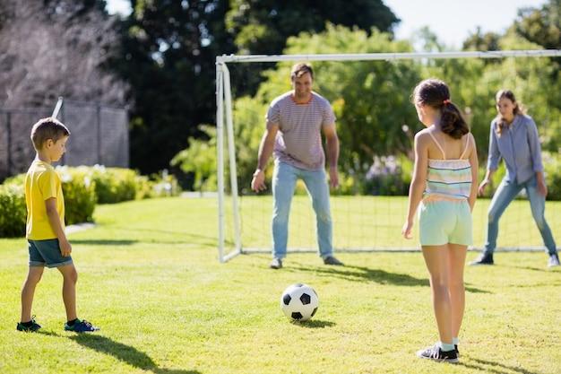 Famille jouant au football ensemble dans le parc