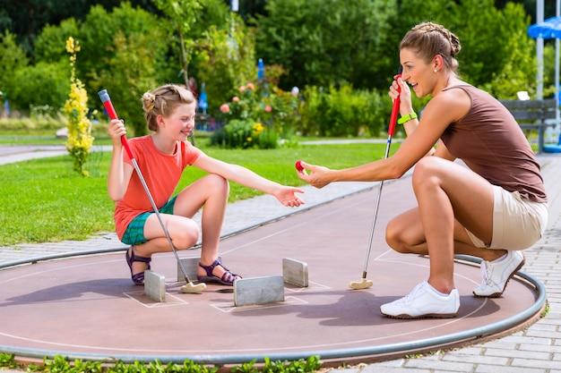 Famille jouant au golf miniature en été